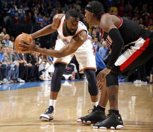 photo - Oklahoma City's James Harden (13) looks to get by Portland's Gerald Wallace (3) during the NBA game between the Oklahoma City Thunder and the Portland Trailblazers, Sunday, March 27, 2011, at the Oklahoma City Arena. Photo by Sarah Phipps, The Oklahoman