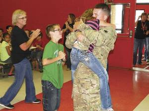 Photo - Kaben Skold leaps into the arms of her dad, Warrant Officer John Skold, while her brother, Morgan, waits his turn. (Muskogee Phoenix photo)