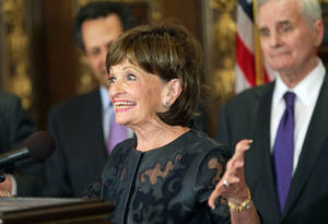 Photo - Super Bowl bid co-chair Marilyn Carlson Nelson shows her enthusiasm during a news conference at the state Capitol, Wednesday, May 21, 2014, in St. Paul. Minn., where Gov. Mark Dayton, right, hosted the presentation leaders who helped bring the NFL 2018 Super Bowl football game to Minneapolis. (AP Photo/Jim Mone)