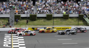 Photo - Brad Keselowski (2) and Dale Earnhardt Jr. (88) race across the line on a late race restart during the NASCAR Sprint Cup series Pocono 400 auto race, Sunday, June 8, 2014, in Long Pond, Pa. Dale Earnhardt Jr. won and Keselowski was second. (AP Photo/Mel Evans)