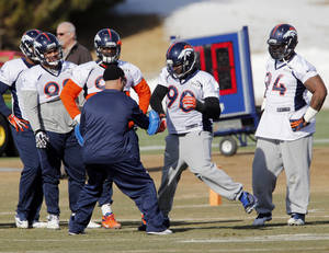 Photo - Denver Broncos defensive end Shaun Phillips (90) works on drills as other defensive linemen look on during practice for the football team's NFL playoff game against the San Diego Chargers at the Broncos training facility in Englewood, Colo., on Thursday, Jan. 9, 2014. (AP Photo/Ed Andrieski)