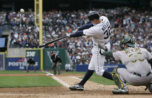 photo -   Detroit Tigers' Don Kelly hits a sacrifice fly to right to score teammate Omar Infante during the ninth inning of Game 2 of the American League division baseball series against the Oakland Athletics, Sunday, Oct. 7, 2012, in Detroit. (AP Photo/Duane Burleson)