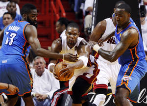 Photo - Miami's Chris Bosh (1) works between Oklahoma City's James Harden (13) and  Kendrick Perkins (5) during Game 3 of the NBA Finals between the Oklahoma City Thunder and the Miami Heat at American Airlines Arena, Sunday, June 17, 2012. Photo by Bryan Terry, The Oklahoman