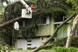 Photo - A worker removes a tree that had fallen on a home during a tornado in Madison, Wis., Wednesday, June 18, 2014. Another round of severe storms knocked down trees and power lines in and around Madison on Wednesday, a day after tornadoes caused extensive damage in the area. (AP Photo/Wisconsin State Journal, Amber Arnold)