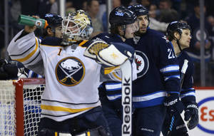 Photo - Winnipeg Jets' Devin Setoguchi, Jacob Trouba, Chris Thorburn and Olli Jokinen, from left at rear, celebrate after Trouba scored on Buffalo Sabres goaltender Jhonas Enroth (1) during the second period of an NHL hockey game in Winnipeg, Manitoba, Tuesday, Dec. 31, 2013. (AP Photo/The Canadian Press, Trevor Hagan)