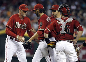 Photo - Arizona Diamondbacks manager Kirk GIbson, left, takes the fall from pitcher Mike Bolsinger as catcher Miguel Montero looks on during the eighth inning of a baseball game against the San Francisco Giants, Sunday, June 22, 2014, in Phoenix. (AP Photo/Matt York)