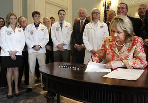 Photo - Oklahoma State University Center for Health Sciences medical students and staff look on as Gov. Mary Fallin signs a bill Wednesday that provides about $3 million to create residency programs at hospitals in rural, underserved areas across the state at the state Capitol in Oklahoma City, Wednesday, June 6 2012. Photo By Steve Gooch, The Oklahoman