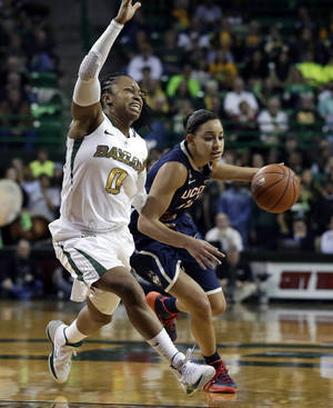 Photo - Baylor's Odyssey Sims (0) attempts to cut off a drive around the perimeter by Connecticut's Bria Hartley (14) in the first half of an NCAA basketball game, Monday, Jan. 13, 2014, in Waco, Texas. (AP Photo/Tony Gutierrez)