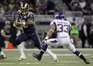 Photo - St. Louis Rams running back Steven Jackson, left, runs for an 8-yard gain as Minnesota Vikings strong safety Jamarca Sanford gives chase during the third quarter of an NFL football game Sunday, Dec. 16, 2012, in St. Louis. (AP Photo/Seth Perlman)