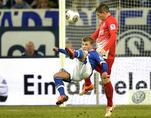 Photo - Schalke's Max Meyer, left, performs a bicycle kick  during the German Bundesliga soccer match between FC Schalke 04 and SC Freiburg in Gelsenkirchen, Germany, Sunday, Dec. 15, 2013. (AP Photo/Martin Meissner)