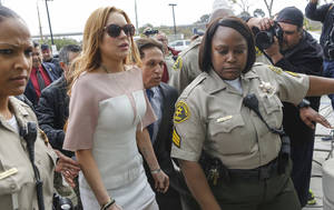 Photo - Actress Lindsay Lohan arrives at the Los Angeles Superior court Monday, March 18, 2013. Lohan is charged with three misdemeanor counts stemming from a crash on Pacific Coast Highway. She is charged with willfully resisting, obstructing or delaying an officer, providing false information to an officer and reckless driving. She is also accused of violating her probation in a misdemeanor jewelry theft case. (AP Photo/Damian Dovarganes)