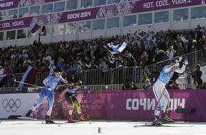 Photo - Sweden's Charlotte Kalla, right, gold, Finland's Krista Lahteenmaki, left, silver, and Germany's Denise Herrmann, bronze, ski on the finish straight during the women's 4x5K cross-country relay at the 2014 Winter Olympics, Saturday, Feb. 15, 2014, in Krasnaya Polyana, Russia. (AP Photo/Matthias Schrader)