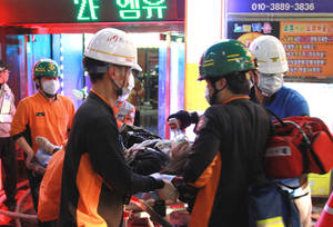 Photo -   Rescue workers carry an injured person on a stretcher from a karaoke bar, where a fire broke out, in Busan, South Korea, Saturday, May 5, 2012. Nine people were reportedly killed in the blaze. (AP Photo/Yonhap) KOREA OUT