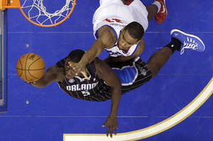 Photo - Orlando Magic's Victor Oladipo (5) goes up for a shot against Philadelphia 76ers' Hollis Thompson (31) during the first half of an NBA basketball game, Tuesday, Dec. 3, 2013, in Philadelphia. (AP Photo/Matt Slocum)