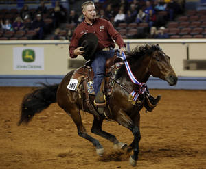 Photo - Corey Cushing, of Scottsdale, Ariz., rides in on Rising Starlight, the 2012 AQHA Superhorse, during the American Quarter Horse championship at the Oklahoma State Fair Park in Oklahoma City, Saturday, Nov. 17, 2012.  Photo by Garett Fisbeck, The Oklahoman