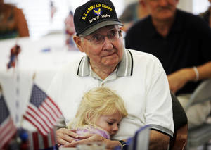 Photo - John Martin, a World War II veteran of the Army Air Force, gets a hug from a family friend's granddaughter Dacie Jo Kersey, 4, after he received three medals for his service in the Army Air Force at his 90th birthday party on July 7, 2013. Photo by KT KING, The Oklahoman