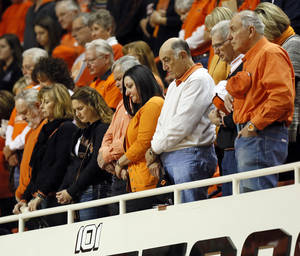 Photo - OSU fans observe a moment of silence for the ten men who died in the 2001 plane crash, before an NCAA men's basketball game between Oklahoma State University (OSU) and West Virginia at Gallagher-Iba Arena in Stillwater, Okla., Saturday, Jan. 26, 2013. Photo by Nate Billings, The Oklahoman