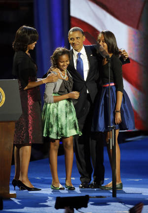 Photo -   President Barack Obama walks out of the stage with his wife Michelle and daughters Sasha and Malia at his election night party Wednesday, Nov. 7, 2012, in Chicago. President Obama defeated Republican challenger former Massachusetts Gov. Mitt Romney. (AP Photo/Pablo Martinez Monsivais)