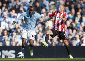 Photo -   Manchester City's Mario Balotelli, left, fights for the ball against Sunderland's Sebastian Larsson during their English Premier League soccer match at The Etihad Stadium, Manchester, England, Saturday, Oct. 6, 2012. (AP Photo/Jon Super)