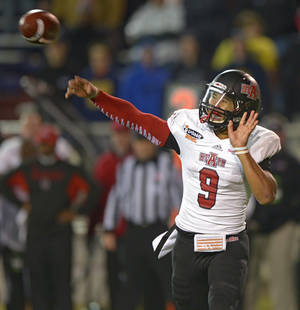 Photo - Arkansas State quarterback Fredi Knighten (9) passes against Ball State in the fourth quarter of the GoDaddy Bowl NCAA college football game in Mobile, Ala., Sunday, Jan. 5, 2014.  Arkansas State defeated Ball State, 23-20. (AP Photo/G.M. Andrews)