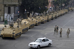 "Photo - Egyptian army soldiers take their positions on top and next to their armored vehicles while guarding an entrance to Tahrir Square, in Cairo, Friday, Aug. 16, 2013. Egypt is bracing for more violence after the Muslim Brotherhood called for nationwide marches after Friday prayers and a ""day of rage"" to denounce this week's unprecedented bloodshed in the security forces' assault on the supporters of the country's ousted Islamist president that left more than 600 dead. (AP Photo/Hassan Ammar)"