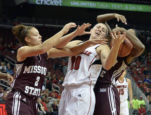 Photo - Louisville's Sara Hammond, center, battles Missouri State's Lexi Hughes, left and Bry Snow for a rebound during the first half of an NCAA college basketball game Tuesday, Dec. 3, 2013, in Louisville, Ky. (AP Photo/Timothy D. Easley)
