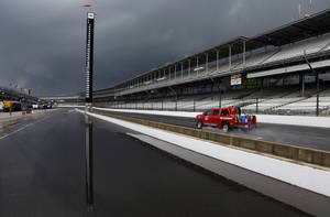 Photo - The scoring pylon is reflected in standing water in the pits area as heavy storms halted practice for the Indianapolis 500 IndyCar auto race at the Indianapolis Motor Speedway in Indianapolis, Tuesday, May 13, 2014. (AP Photo)