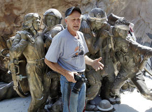"Photo - Gareth Andrews, sculptor, stands next to his veterans' memorial monument on Tuesday in Norman. The 13-foot-tall bronze will be taken to Minnesota after completion at The Crucible Foundary. ""Shoulder to Shoulder Even the Fallen Stand Tall"" depicts life-size military figures of varied ethnic backgrounds in front of a larger-than-life eagle. The men and women portrayed in the memorial represent all five branches of the United States armed forces and their affiliated women's corps. Photo by Steve Sisney, The Oklahoman"