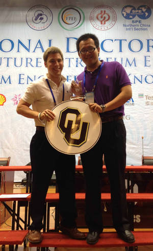 photo - Jon Clark and Jiang Zheng, recent graduates from the University of Oklahoma, pose with a first-place trophy from PetroBowl 2012. PHOTO PROVIDED.