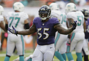 Photo - Baltimore Ravens outside linebacker Terrell Suggs (55) celebrates after sacking Miami Dolphins quarterback Ryan Tannehill (17) during the second half of an NFL football game, Sunday, Oct. 6, 2013, in Miami Gardens, Fla. The Ravens defeated the Dolphins 26-23. (AP Photo/Wilfredo Lee)