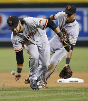 Photo - San Francisco Giants' Brandon Crawford, front, can't field a base hit by Arizona Diamondbacks' Gerardo Parra, as Ehire Adrianza backs him up during the seventh inning of a baseball game, Saturday, June 21, 2014, in Phoenix. (AP Photo/Matt York)