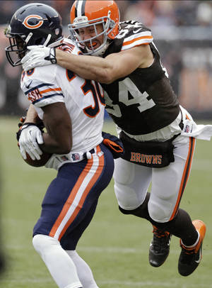 Photo - Cleveland Browns tight end Jordan Cameron (84) tackles Chicago Bears cornerback Zack Bowman after an interception in the first half of an NFL football game, Sunday, Dec. 15, 2013, in Cleveland. (AP Photo/Tony Dejak)