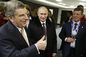 Photo - Russian President Vladimir Putin, center, talks with International Olympic Committee President Thomas Bach, left, and Deputy Prime Minister Dmitry Kozak, right, in the presidential lounge following the opening ceremony of the 2014 Winter Olympics, Friday, Feb. 7, 2014, in Sochi, Russia. (AP Photo/David Goldman, Pool)
