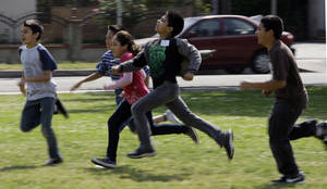 Photo - FILE - This May 10, 2011 file photo shows children at Tracy Elementary School running across a field as they take part in after-school exercise activities on the campus in Baldwin Park, Calif. Reading, writing, `rithmetic _ and PE?  The prestigious Institute of Medicine is recommending that schools provide opportunities for at least 60 minutes of physical activity each day for students and treat physical education as a core subject. The report says only about half of the nation's youngsters are getting at least an hour of vigorous or moderate physical activity every day. (AP Photo/Reed Saxon, File)