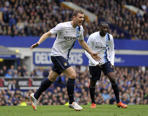Photo - Manchester City's Edin Dzeko, left, celebrates after scoring the second goal of the game during their English Premier League soccer match against Everton at Goodison Park in Liverpool, England, Saturday May 3, 2014. (AP Photo/Clint Hughes)