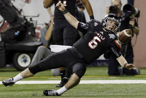 Photo - Northern Illinois quarterback Jordan Lynch falls into the end zone after a touchdown during the second half of an NCAA college football game against Bowling Green at the Mid-American Conference championship in Detroit, Friday, Dec. 6, 2013. (AP Photo/Carlos Osorio)