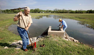 photo - Bob Martin, fisheries biologist for Okla. City Parks and Recreation, and Mike Veasey, fisheries technician, readying ponds at the H.B. Parsons Fish Hatchery Thursday, April 22, 2010, to raise 600,000 walleye for stocking into Lake Hefner in Oklahoma City. Photo by Paul B. Southerland, The Oklahoman