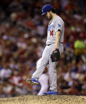 Photo - Los Angeles Dodgers starting pitcher Dan Haren kicks at the mound as he waits to be removed from a baseball game against the St. Louis Cardinals during the fifth inning Friday, July 18, 2014, in St. Louis. (AP Photo/Jeff Roberson)
