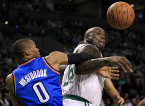 Photo - Boston Celtics center Shaquille O'Neal, right, loses control of the ball against Oklahoma City Thunder guard Russell Westbrook during Friday's game. AP PHOTO