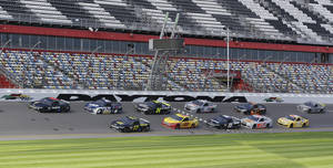 photo - FILE - In this Jan. 11, 2013, file photo, a pack of cars drives past the start/finish line moments before a wreck on the backstretch during NASCAR auto race testing at Daytona International Speedway in Daytona Beach, Fla. There's a buzz about NASCAR and the season-opening Daytona 500 that has nothing to do with an exploding jet dryer or a well-timed tweet. NASCAR's new Gen-6 race car makes its long-awaited debut and the success of the 2013 season could depend heavily on its performance. (AP Photo/John Raoux, File)