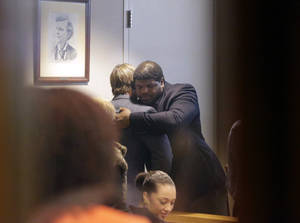 Photo - Former Dallas Cowboys NFL football player Josh Brent, right, hugs Dallas Cowboys linebacker Sean Lee in court after closing arguments in his intoxication manslaughter trial Tuesday, Jan. 21, 2014, in Dallas. The jury has begun deliberating in Brent's intoxication manslaughter trial after lawyers wrapped up their closing arguments Tuesday morning. Prosecutors accuse the former defensive tackle of drunkenly crashing his Mercedes near Dallas during a night out in December 2012, killing his good friend and teammate, Jerry Brown. (AP Photo/LM Otero)