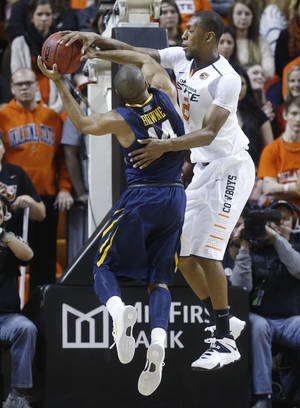 Photo - West Virginia guard Gary Browne (14) is fouled by Oklahoma State post Kamari Murphy (21) as he shoots in the second half of an NCAA college basketball game in Stillwater, Okla., Saturday, Jan. 25, 2014. Oklahoma State won 81-75.(AP Photo/Sue Ogrocki)