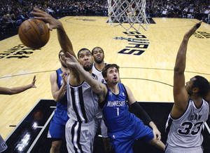 Photo - San Antonio Spurs' Tim Duncan, left, blocks Minnesota Timberwolves' Alexey Shved (1) as he tries to score during the first half on an NBA basketball game, Friday, Dec. 13, 2013, in San Antonio.  (AP Photo/Eric Gay)
