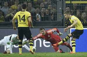 Photo - Dortmund's Marco Reus, right, scores a goal against Wolfsburg goalkeeper Max Gruen during  the German Bundesliga soccer match between Borussia Dortmund and VfL Wolfsburg in Dortmund,  Germany, Saturday, April 5, 2014, 2014. (AP Photo/Martin Meissner)