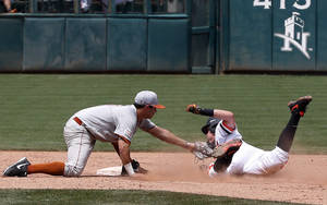 Photo - Oklahoma State's Craig McConaughy, right, is tagged out by Texas shortstop C.J. Hinojosa, left, in the eighth inning of a game in the Big 12 conference NCAA college baseball tournament in Oklahoma City, Saturday, May 24, 2014. Oklahoma State won 3-1, forcing a second game between the two teams. (AP Photo/Sue Ogrocki)