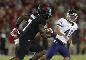 Photo - Stanford's Ty Montgomery, left, returns the opening kickoff for a touchdown against Washington during the first half of an NCAA college football game in Stanford, Calif., Saturday, Oct. 5, 2013. At right is Washington's Kevin Anderson. (AP Photo/George Nikitin)