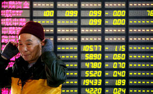 Photo -   An investor smiles in front of the stock price monitor at a private securities company Tuesday, Nov. 27, 2012 in Shanghai, China. Asian stock markets rose Tuesday after talks over Greece's financial crisis ended with an agreement on how to reduce its debt load, paving the way for the cash-strapped country to receive the next installment of a bailout loan. (AP Photo)