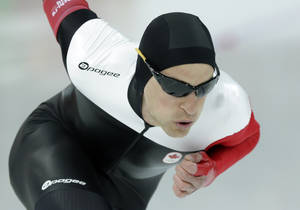 Photo - Silver medallist Canada's Denny Morrison competes in the men's 1,000-meter speedskating race at the Adler Arena Skating Center during the 2014 Winter Olympics in Sochi, Russia, Wednesday, Feb. 12, 2014. (AP Photo/Matt Dunham)