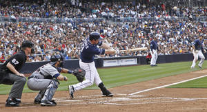 Photo - San Diego Padres' Jedd Gyorko lofts a sacrifice fly to left field that scores Chris Denorfia from third in the first inning of a baseball game against the Detroit Tigers Saturday, April 12, 2014, in San Diego. (AP Photo/Lenny Ignelzi )