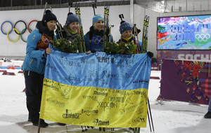 Photo - Ukraine's relay team Vita Semerenko, Juliya Dzhyma,  Olena Pidhrushna and Valj Semerenko, from left, celebrate with Ukrainian flag with writings on it after winning the gold during the flower ceremony of the women's biathlon 4x6k relay at the 2014 Winter Olympics, Friday, Feb. 21, 2014, in Krasnaya Polyana, Russia. (AP Photo/Kirsty Wigglesworth)